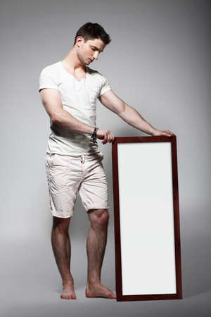 shoeless: Shoeless Man Displaying White Board with Blank Space Stock Photo