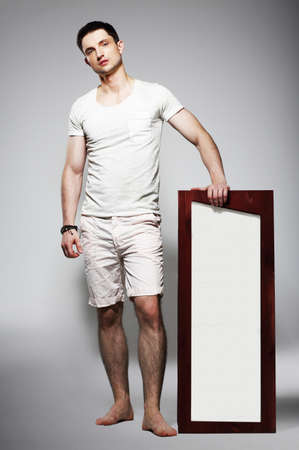 plackard: Full Length of Young Barefoot Man in White Shorts with Plackard Stock Photo