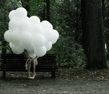 suspenso: El sentimentalismo. Nostalgia. Mujer sola con globos de aire que se sienta en banco en el parque