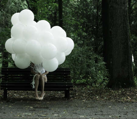 suspense: Sentimentality. Nostalgia. Lonely Woman with Air Balloons sitting on Bench in the Park