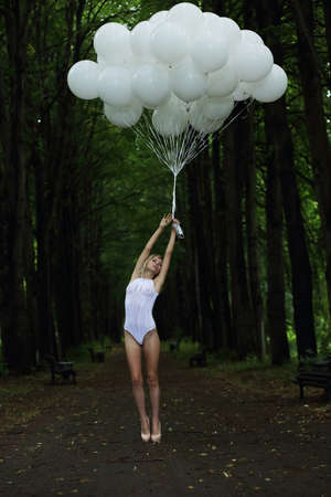 oudoor: Fantasy  Nostalgic Svelte Woman with Air Balloons on Country Road Stock Photo