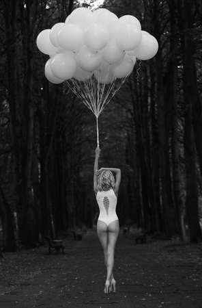 dismal: Melancholy. Lonely Woman with Balloons in Dark and Gloomy Forest