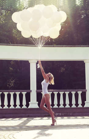 Holiday. Happy Carefree Woman Launching Bunch of Air Balloons photo
