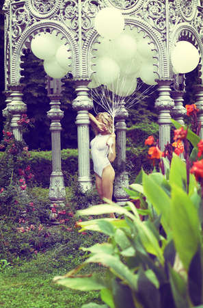 Sentiment. Beautiful Relaxed Blonde holding Air Balloons in the Garden photo