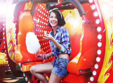 sweetened: Lifestyle. Young Happy Woman Eating Sweetened Cotton Candy in Funfair Stock Photo