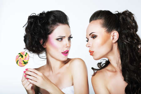 rapturous: Fantasy. Woman Teasing another with Lollipop Stock Photo