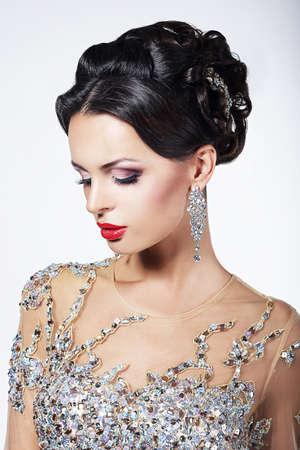 Partido formal. Modelo de manera magnífica en vestido brillante ceremonial con las joyas
