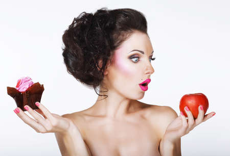 candy apple: Surprised Funny Woman Decides between Apple and Cake Stock Photo