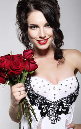 Fragrance. Beautiful Young Woman Holding Bouquet of Red roses. Valentines Day photo