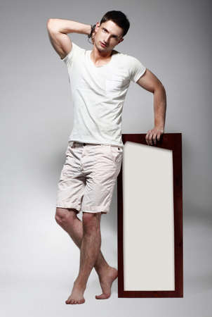 Elegant Young Man in White Cotton Clothes with Board Standing photo