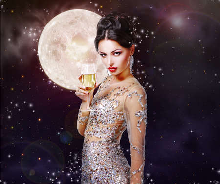 Romantic girl in the beautiful dress with a glass of champagne against the night sky with magical stars and moon