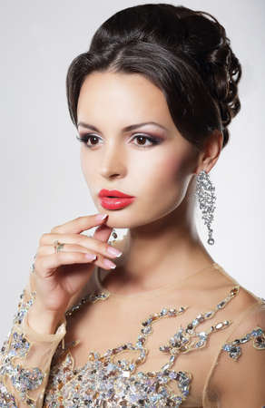 Portrait of a gorgeous young woman with evening hairstyle and glamourous makeup with red lips wearing a silver earring. Stock Photo - 23728258