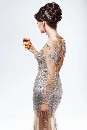 Elegant Woman in Silver-Golden Dress holding Wineglass of Champagne. Luxury photo