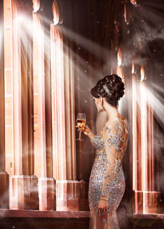 casement: Luxury. Young Woman in Evening Dress with Glass of Champagne Standing at the Window in Sunshine Stock Photo