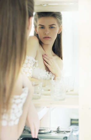 vestal: Expression. Candid Genuine Pensive Woman Reflects in Mirror