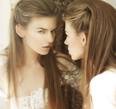 Delusion. Image of Beautiful Woman in Front of a Mirror photo