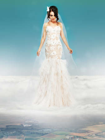 Bride in Wedding White Dress standing on a Cloud and Looking to the Ground photo