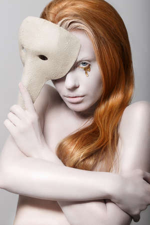 travesty: Stylized Woman with Carnival Venetian Mask. Masquerade. Platinum Makeup with Golden Teardrops Stock Photo