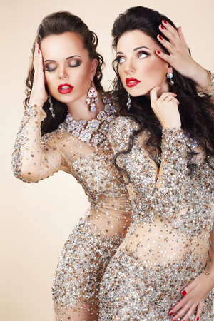 stagy: Two Glamorous Women in Evening Dresses and Jewelry Dancing Stock Photo