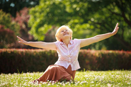 outspread:  Gladness. Meditation. Mature Pleased Woman Relaxing with Outspread Arms Stock Photo