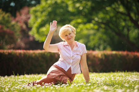 maturity:  Maturity. European White Hair Woman sitting on Grass and having Fun Stock Photo