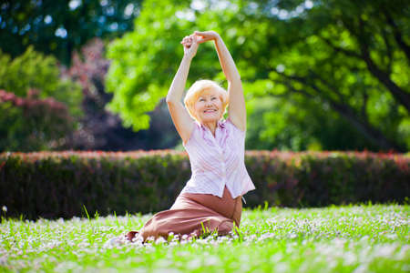 wellness environment: Wellness. Mental Health. Optimistic Old Woman Exercising in Open Air Stock Photo