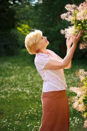 grizzle: Gardening. Gracious Senior Woman and Flowers Stock Photo