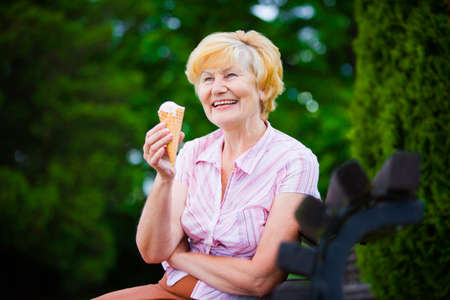 popsicles: Grey-Haired Woman Relaxing with Ice-Cream on Bench in the Park Stock Photo
