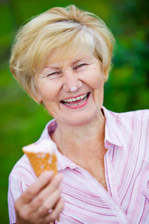 contentment:  Contentment. Jubilant Ecstatic Old Woman Holding Ice-Cream and Laughing