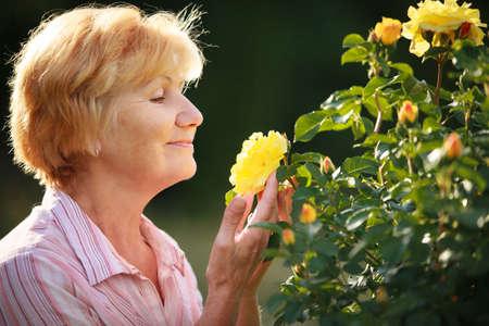 olfato: Expresión. Superior Modelo Mujer con rosas del jardín. Primavera Foto de archivo