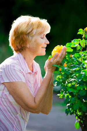 Sentimentality. Mature Pretty Old Lady Smelling Yellow Flower