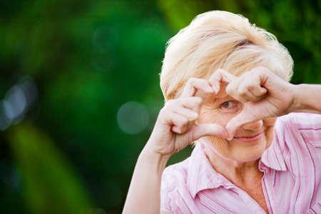 陽性。幸せな面白い年配の女性の心のシンボルを表示