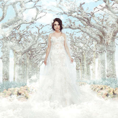 winter wedding: Fantasy  Matrimony  Bride in White Dress over Frozen Winter Trees and Snowflakes