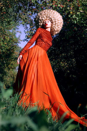 stagy: Fantasy. Artistic Stylized Woman in Trendy Red Dress and Big Frizzy Wig