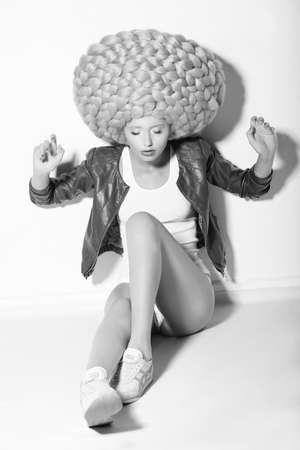 Creativity. Trendy Woman in Huge Fancy Wig sitting on Floor Stock Photo