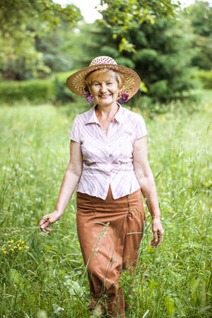 peasant: Serenity. Friendly Senior Peasant Woman in Straw in Meadow Smiling Stock Photo