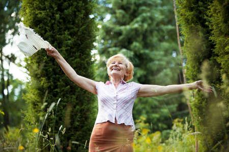 Freedom. Happy Old Lady with Hut smiling in The Garden. Lifestyle Stok Fotoğraf