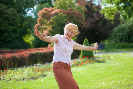 gaiety: Gaiety. Delighted Playful Mature Woman with Outstretched Arms Laughing Outside
