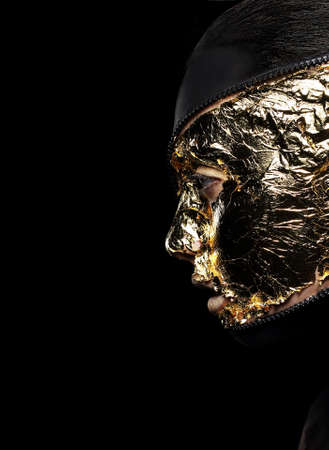 Styled Womans Face Covered Golden Foil over Black Background. Mystery photo