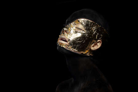 stagy: Fiction. Imagination. Futuristic Creature in Crazy Mystic Mask and Gilt Stock Photo