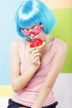 peruke: Trendy Woman in Blue Wig and ping Glasses Eating Watermelon