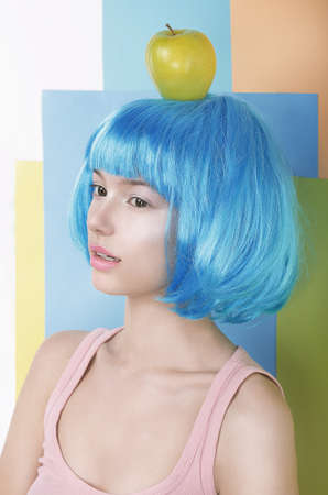 periwig: Imagination. Asian Woman in Blue Wig with Apple on her Head Stock Photo