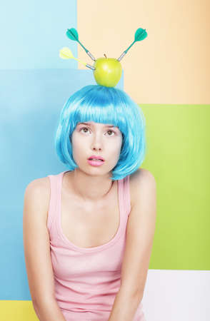 periwig: Stylized Woman with Apple on her Blue Haired Head. Series of Photos Stock Photo