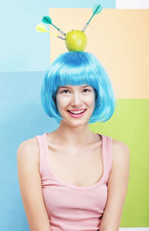 ridiculous: Precision. Amusing Woman in Blue Wig, Green Apple and Darts Stock Photo