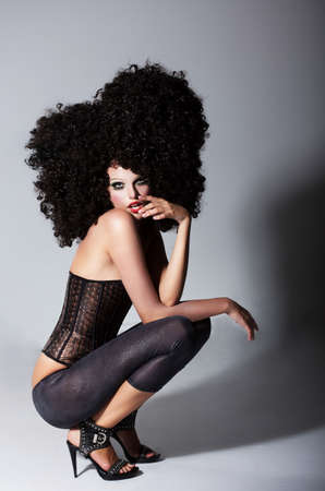 stagy: Updo. Beautiful Woman in Dark Curly Fantastic Wig Sitting. Frizzy Hairstyle