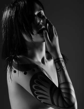 Enigmatic Glamorous Woman Vamp with Tattoo on her Arm photo
