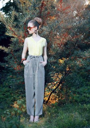 容姿の美しさ。エレガントなパンツ屋外でトレンディなスタイリッシュなファッション モデル