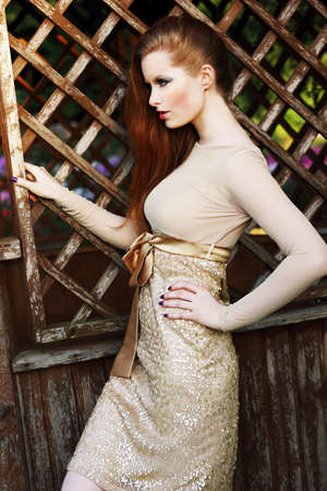 Stylish Glamorous Redhead Woman in Golden Trendy Dress Outside photo