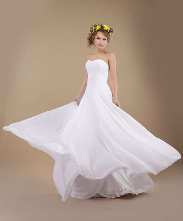 fiancee: Beautiful Fiancee with Vernal Wreath of Flowers in Flying Wedding Dress Stock Photo
