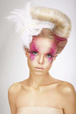 maquillaje de fantasia: Faceart. Rubia con una piel de color de rosa, pestañas postizas y la pluma blanca Foto de archivo